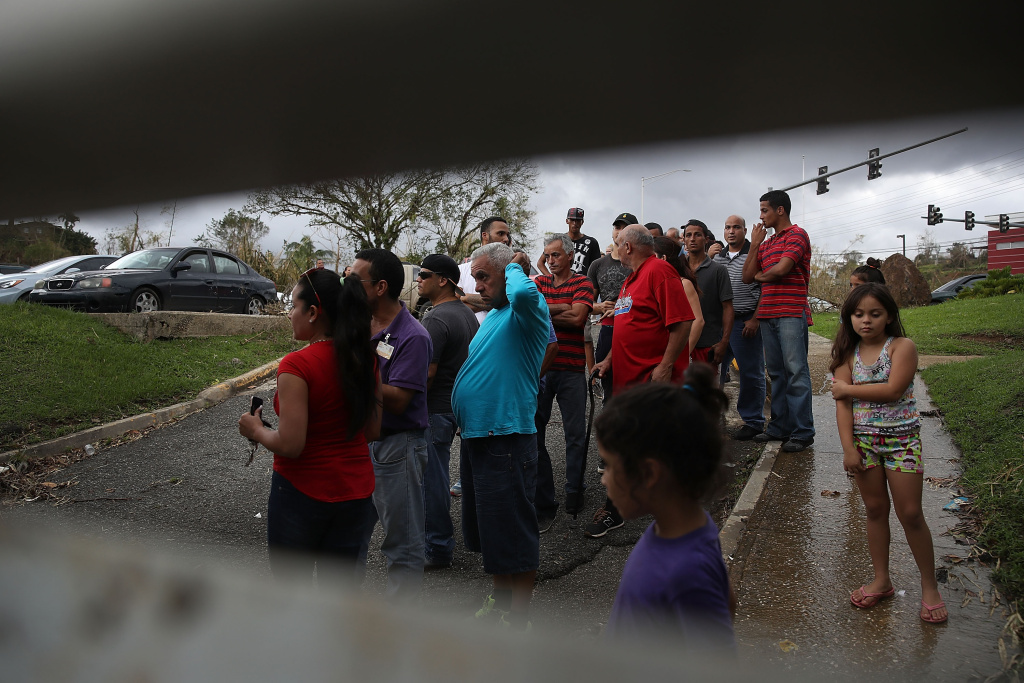 Hurricane survivors watch as Puerto Rican National Guardsmen prepare to deliver food and water from their helicopter on September 29, 2017 in Lares, Puerto Rico.