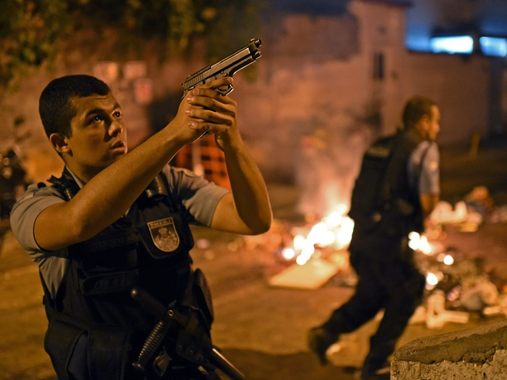 An officer from Brazilian Police Special Forces took aim Tuesday during the violent protest that broke out in one of Rio de Janeiro's slums. People there blame police for a young man's death, and say authorities are clamping down too hard in advance of this June's World Cup soccer tournament and the 2016 Summer Olympics, both of which will be held in Brazil.