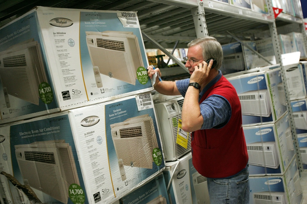 Customer Service Associate Doug Ferket talks to a customer on the phone regarding available in-window air conditioners at the Lowe's home improvement store August 2, 2006 in Arlington Heights, Illinois.