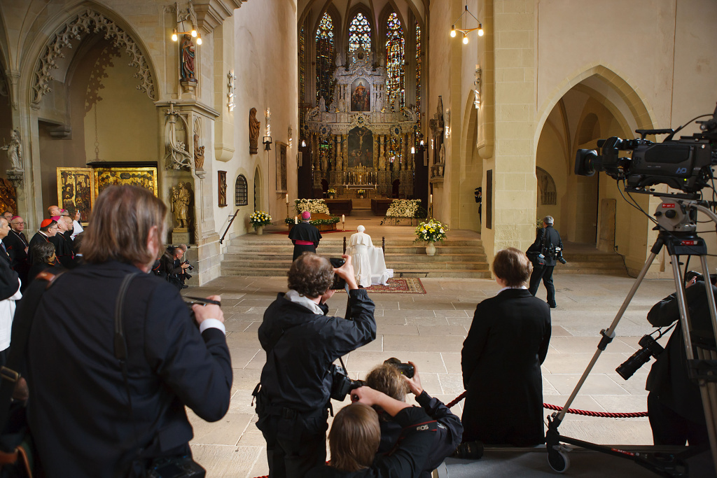 Media gather whilst Pope Benedict XVI kneels to pray at the main altar of the Dom cathedral on Sept. 23, 2011 in Erfurt, Germany.