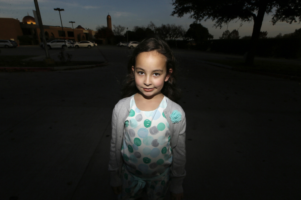 Sofia Yassini, 8, poses for a photo outsider a mosque in Richardson, Texas, Friday, Dec. 11, 2015. After seeing presidential candidate Donald Trump call on television for barring Muslims from entering the country, the 8-year-old started packing her favorite things and checking the locks on the doors because, in her mind, Donald Trump's push to ban Muslims entering the country meant the Army would come and rip her family from their home. Trump's remarks in the wake of the Dec. 2  shooting attack in San Bernardino have stoked similar fears in Muslim children across the U.S. Their young minds, parents say, are confused about who the screaming man on TV is, what he's saying about their faith and why thousands of their fellow Americans are cheering him on.