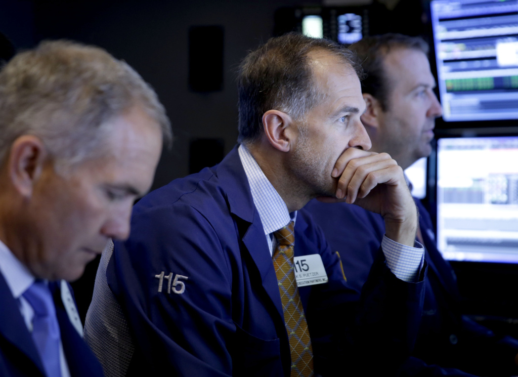 Trader Mark Puetzer, center, works on the floor of the New York Stock Exchange, Thursday, July 9, 2015  in New York. U.S. stocks opened with big gains, bouncing back from a loss the day before, as investors hoped that last-ditch talks would produce an agreement between Greece and its creditors. (AP Photo/Seth Wenig)