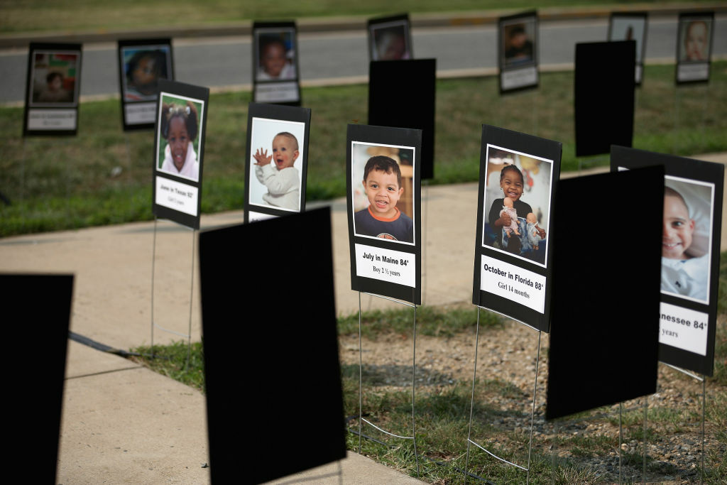 Stock photographs representing children who have died after being left unattended in vehicles are on display during a news conference to launch the