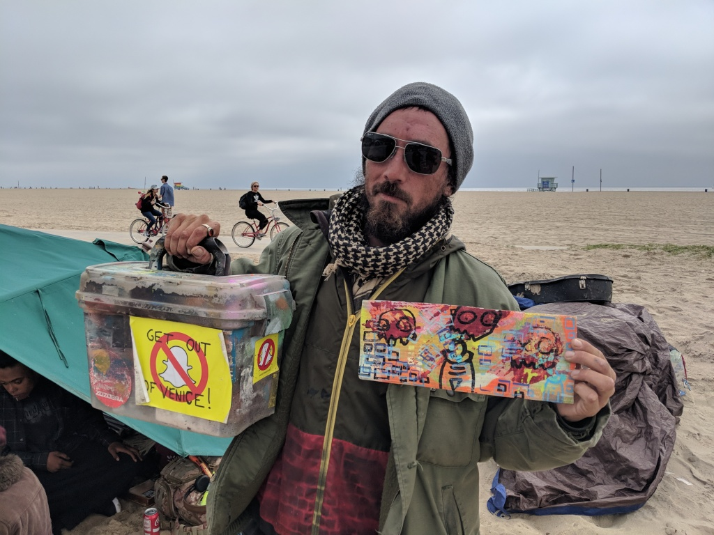 Street artist Reed Segovia holds up some of his art, as well as a sticker protesting Snap's presence in Venice.