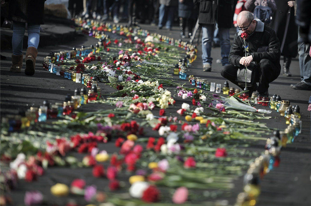 People add flowers to a huge line of flowers and candles leading to the barricades in central Kiev on February 24, 2014. Ukraine issued an arrest warrant for ousted president Viktor Yanukovych on Monday as the country's new rulers launched a probe over the 'mass murder' of protesters in a week of carnage in Kiev.
