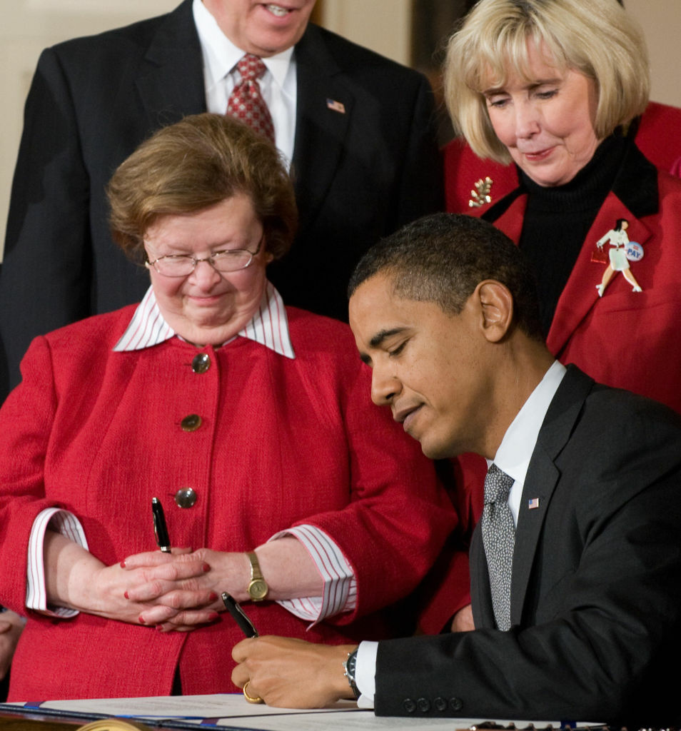 US President Barack Obama, with Lilly Ledbetter (R) and Maryland Senator Barbara Mikulski (L), signs the Lilly Ledbetter Fair Pay Act in the East Room of the White House in Washington, DC, January 29, 2009. The wage discrimination bill, which allows employees more time to file a claim, is named after Lilly Ledbetter, a retired worker at a Goodyear factory in Alabama who discovered she was paid less than her male counterparts.