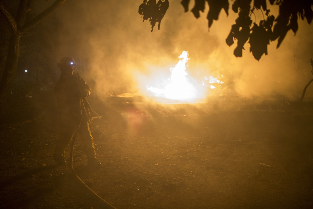 A firefighter picks up hose next to a burning structure in the early morning hours on October 14, 2017 in Sonoma, California.