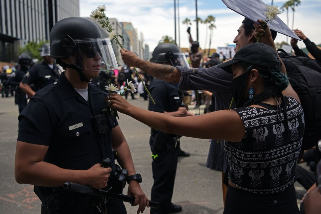 A protester puts a flower in the pocket of an LAPD officer during a demonstration over the death of George Floyd in Hollywood, California on June 2, 2020.