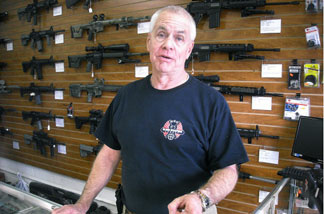 Tom Rompel, the owner of the Black Weapons Armory store in Tucson, Arizona, speaks to customers on January 10, 2011 in front of his wide selection of guns.