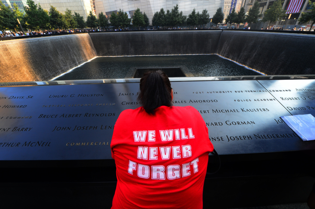 Friends and family members gather at the 9/11 Memorial during ceremonies marking the 12th anniversary of the 9/11 attacks on the World Trade Center on September 11, 2013 in New York City.