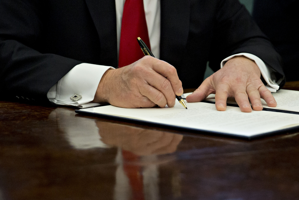 U.S. President Donald Trump signs an executive order in the Oval Office of the White House January 30, 2017 in Washington, DC.