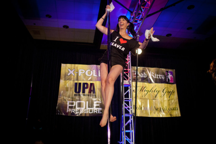 A synchronized pole dancing team performs on the main stage of the International Pole Dancing Convention at the Airport Marriot hotel on June 24, 2012.