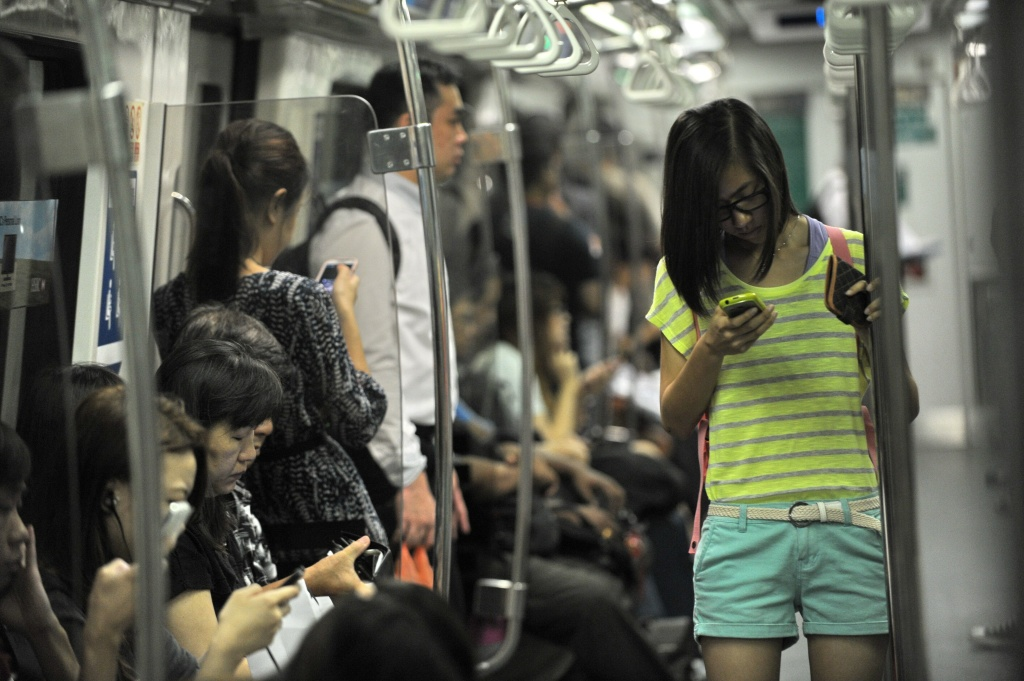 People spend their time on smart phone while travelling in the Mass Rapid Transit train in Singapore on April 30, 2014.