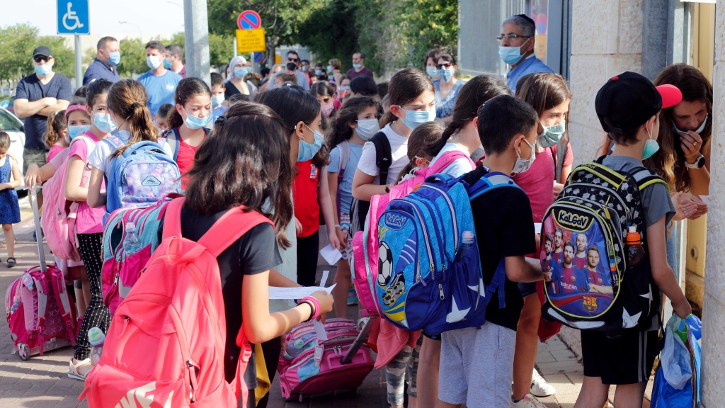 Students wearing masks are outside a school in the Israeli city of Modiin on May 17. Israeli students in all grades went back to school last month.