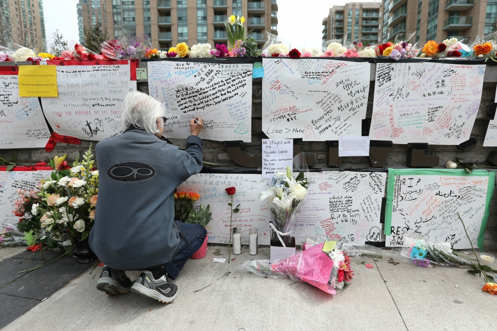 Jack Young leaves a notes on April 24, 2018, at a makeshift memorial for victims in the van attack in Toronto, Ontario.