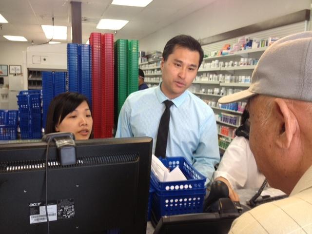 Pharmacist and owner of the  El Monte Pharmacy, Ken Thai, helps a customer.