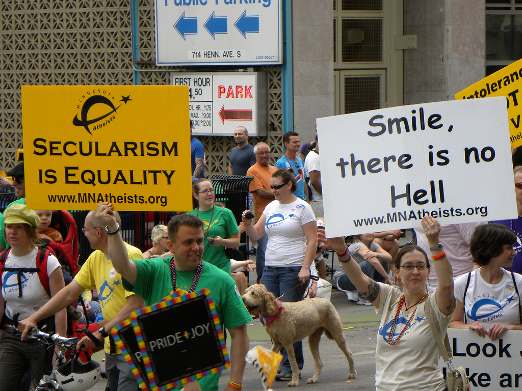 Participants carry signs supporting atheism during the Ashley Rukes LGBT Pride Parade in Minneapolis, Minnesota on June 26, 2011