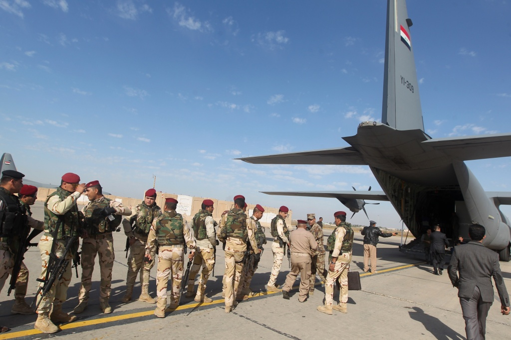 Iraqi army soldiers stand before boarding a military plane in Baghdad to fly to a conference on fighting the Islamic State group attended by Iraq's tribal leaders, militiamen and members of the government in Iraq's mainly Sunni Anbar province, on November 11, 2014. A team of US troops was on the ground in Iraq's Anbar province today as Washington steps up efforts to help Iraqi forces battle the Islamic State jihadist group.
