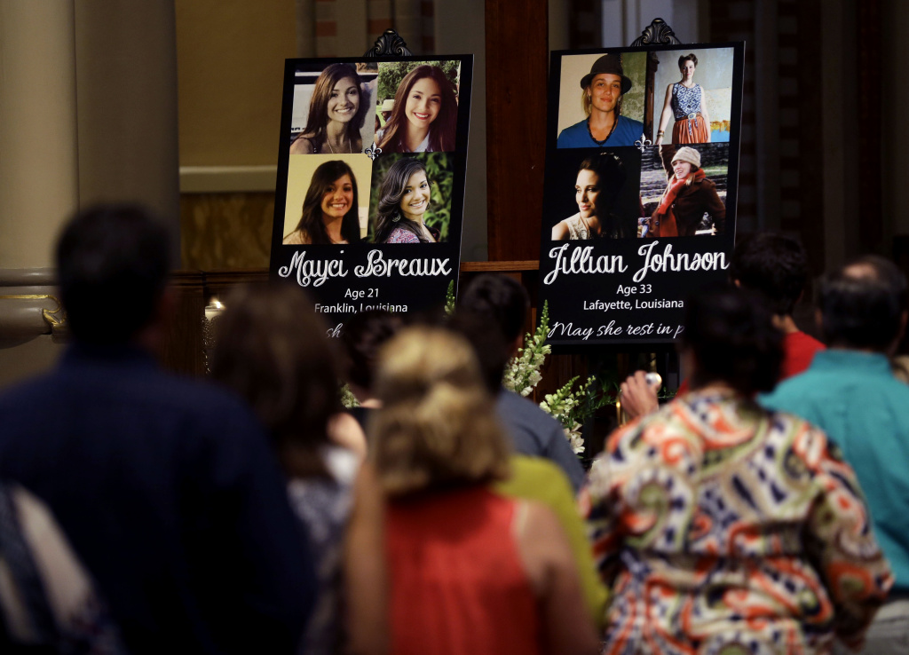 People line up to pay their respects during a prayer service for the victims of The Grand 16 theater shooting at the Cathedral of St. John the Evangelist, in Lafayette, La., Sunday, July 26, 2015. John Russell Houser stood up about 20 minutes into Thursday night's showing of
