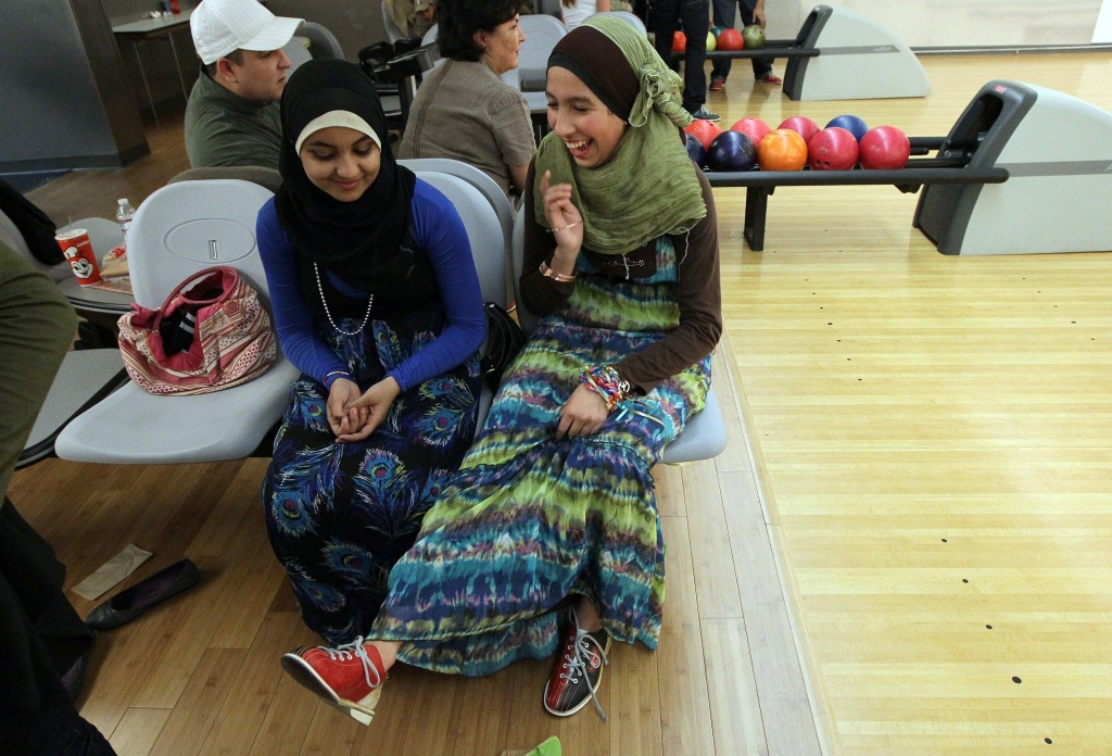 Muslim teenagers Anfal Morsy (L) and Sara Bouabibsa look at their bowling shoes during a group outing at the Yerba Buena Bowling Center in San Francisco, California.
