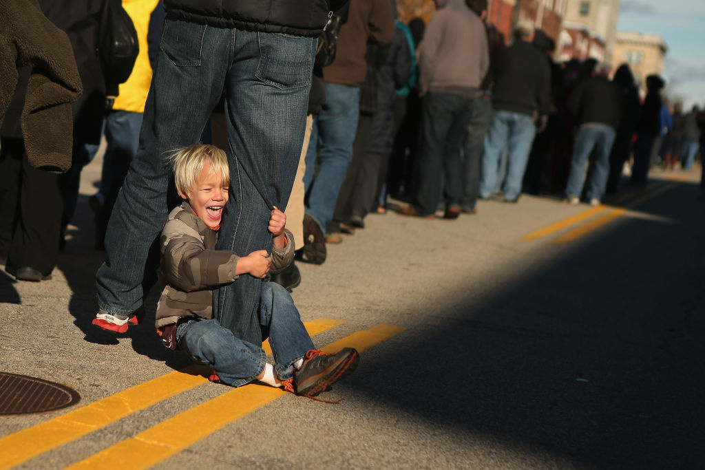 Hudson Schoewe, 4, of Cape Elizabeth, Maine, rides on his father's leg while waiting in line with more than 14,000 people to attend a campaign rally with U.S. President Barack Obama in State Capitol Square November 4, 2012 in Concord, New Hampshire.