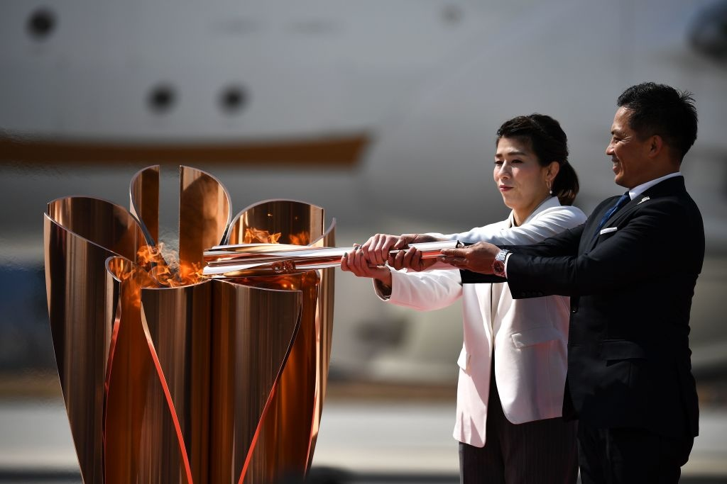 Japanese three-time Olympic gold medallists Saori Yoshida and Tadahiro Nomura light a Tokyo 2020 Olympic cauldron with the Olympic flame, after transporting the flame from Greece, at the Japan Air Self-Defense Force Matsushima Base in Higashimatsushima, Miyagi prefecture on March 20, 2020.
