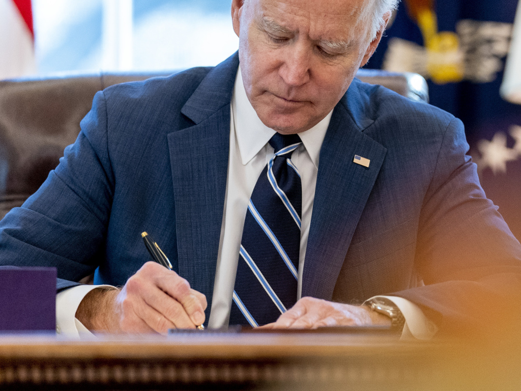 President Biden signs the American Rescue Plan in the Oval Office of the White House on March 11. Included in the plan is a monthly allowance for many American families that could be a potential financial life changer.