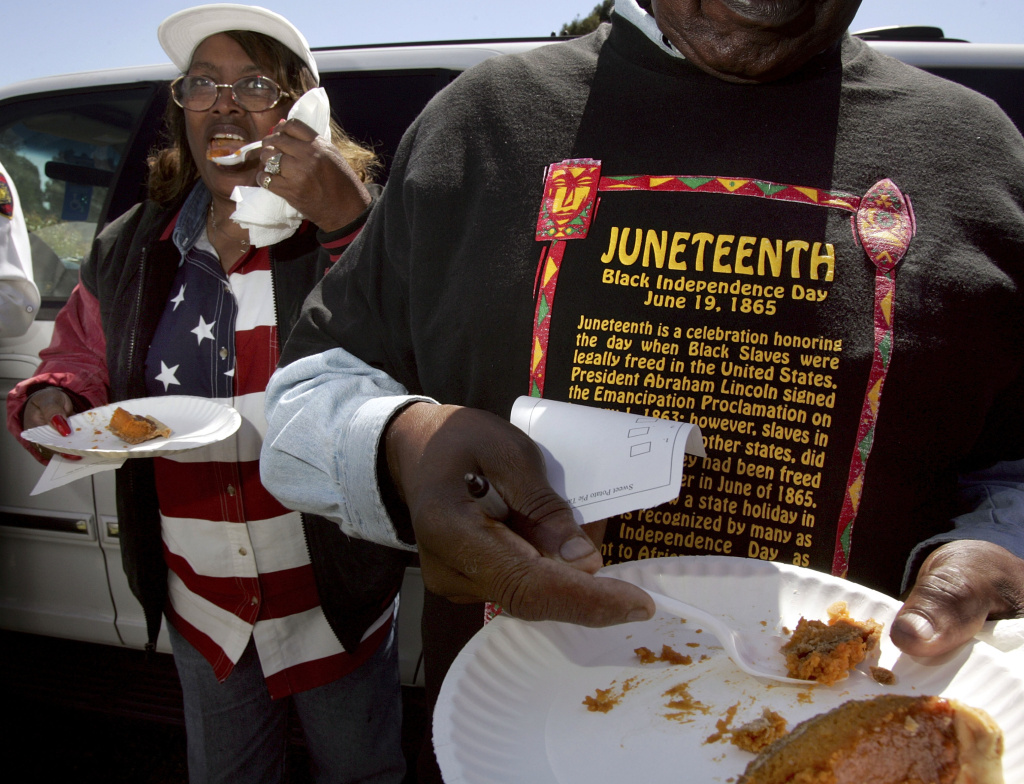 Naomi Williams (left) and D'Emanuel Grosse Sr. (right) taste the sweet potato pie entered in the cook-off contest at the Juneteenth, Black Independence Day celebrations on June 19, 2004 in Richmond, California. The holiday is celebrated in June because slaves in Texas and several other states did not learn of their freedom until June of 1865.