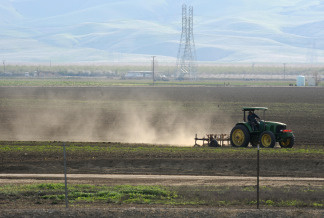 Dust rises as a farmer plows a field in Mendota, California in the state's San Joaquin Valley on March 11, 2009.