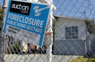 A foreclosure sign hangs on a fence in front of a foreclosed home in California.