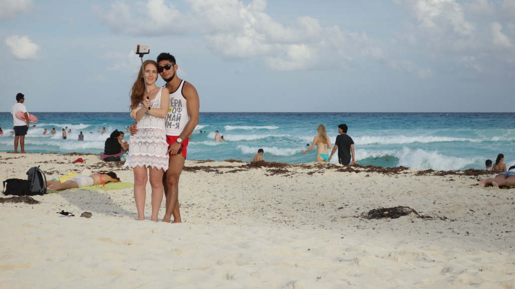 A couple uses a selfie stick on a Mexican beach. As 2015 begins, the selfie stick has invaded American shores, first on the coasts — Times Square is already full of 'em — but soon, places like Mount Rushmore and the Gateway Arch are bound to become selfie stick central.