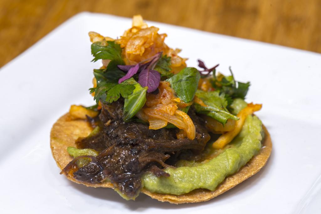 BBQ Korean short rib tostada with Kimchi, herbs and avocado salsa.