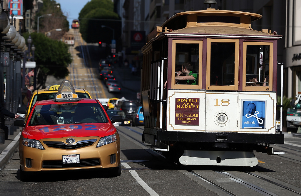A Cable Car passes a line of taxicabs as they wait for fares in front of the St. Francis Hotel on January 21, 2014 in San Francisco, California.