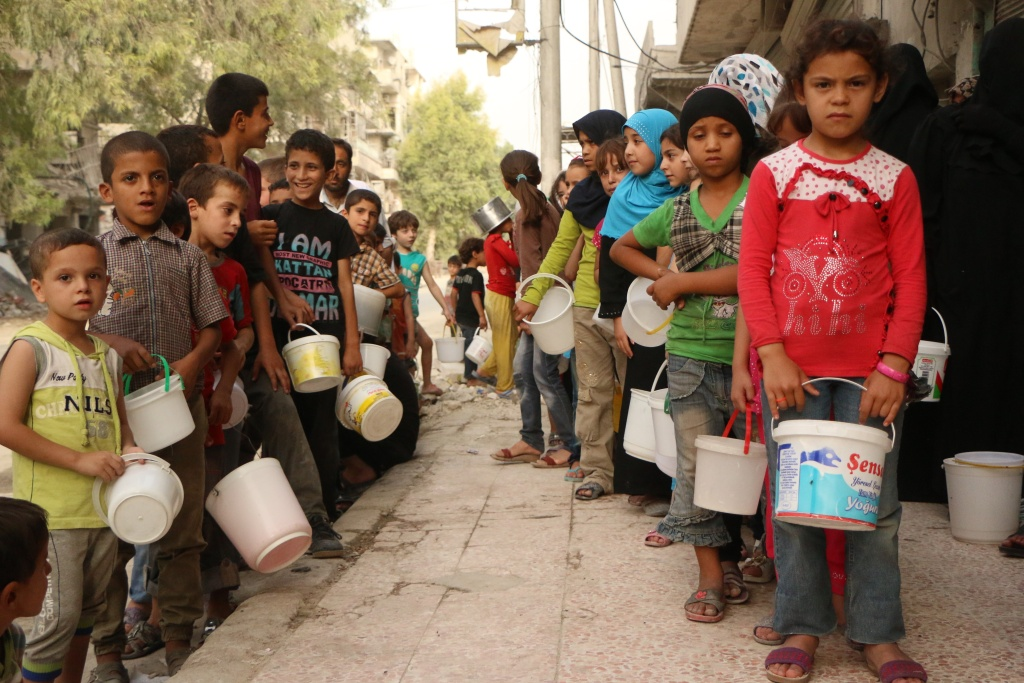 Syrian children, who were displaced with their families from their houses due to the ongoing conflict in Syria, queue up to receive aid food in the rebel side of the northern city of Aleppo, on September 7, 2015