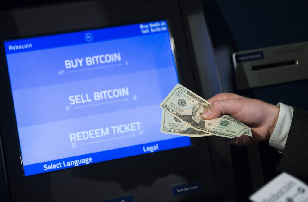 Robocoin CEO Jordan Kelley demonstrates how to buy and sell bitcoins during a demonstration of a Robocoin kiosk on Capitol Hill in Washington, DC, April 8, 2014. Robocoin is the world's first bitcoin kiosk for buying and selling the digital currency. AFP PHOTO / Saul LOEB        (Photo credit should read SAUL LOEB/AFP/Getty Images)