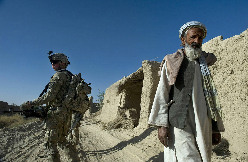 An elderly Afghan man walks past a US Army infantryman carrying a 40-callibre rifle, attached to the 2nd platoon, C-Coy. 1-23 Infantry at Naja-bien village, Panjwai district during a morning operation to find and destroy bomb traps made from IED's on September 23, 2012.