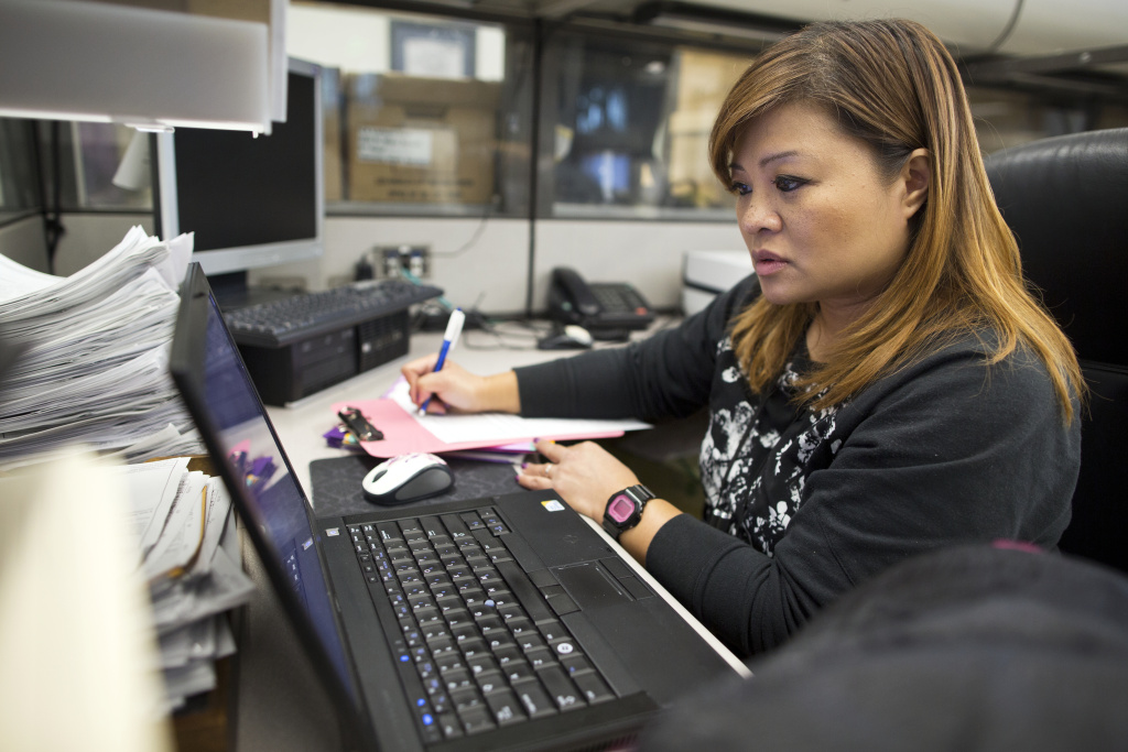 Grace Bescoby, a registered nurse and mental health counselor on the Mental Evaluation Unit's SMART team, looks for possible hospitals where the man in custody could be taken in at the LAPD's Rampart Division on Thursday, Dec. 11, 2014.