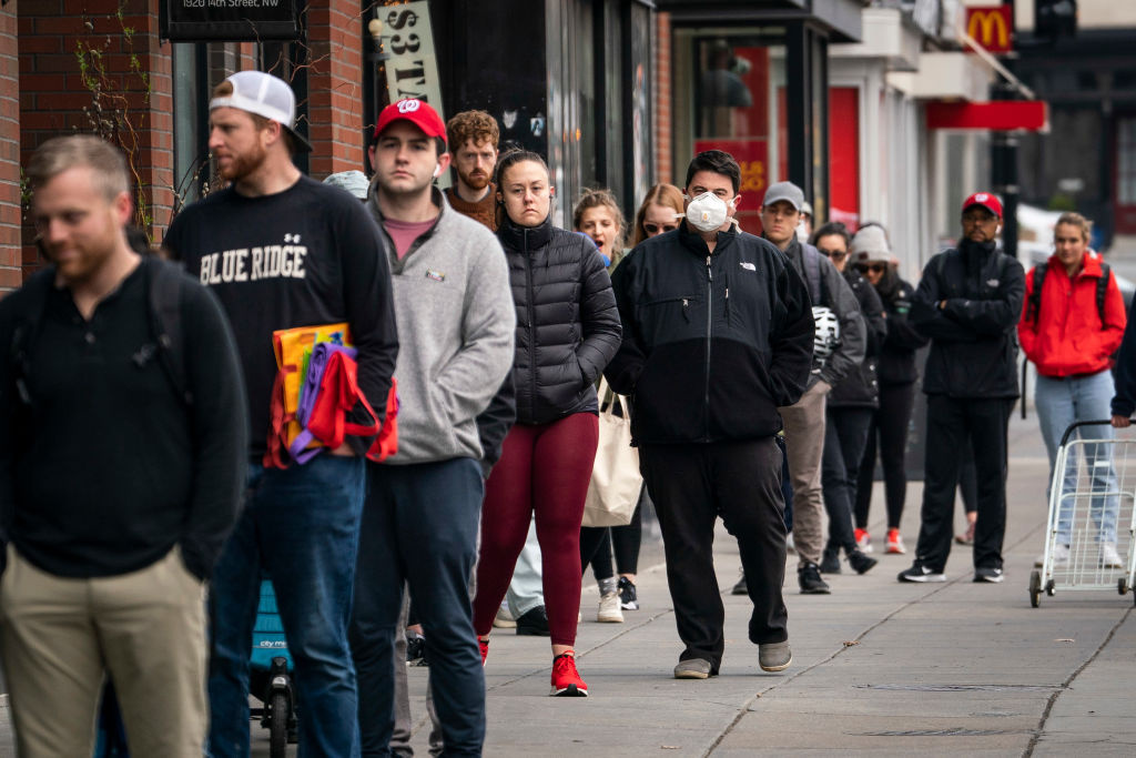 People wait in a line to get into a Trader Joe's grocery store on April 1, 2020 in Washington, DC.