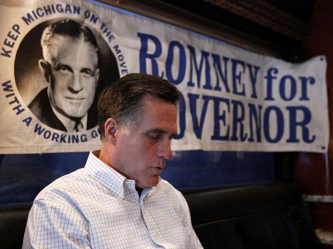 Mitt Romney reads on his campaign bus earlier this year. A 1960s campaign poster supporting his father, George, is behind him.