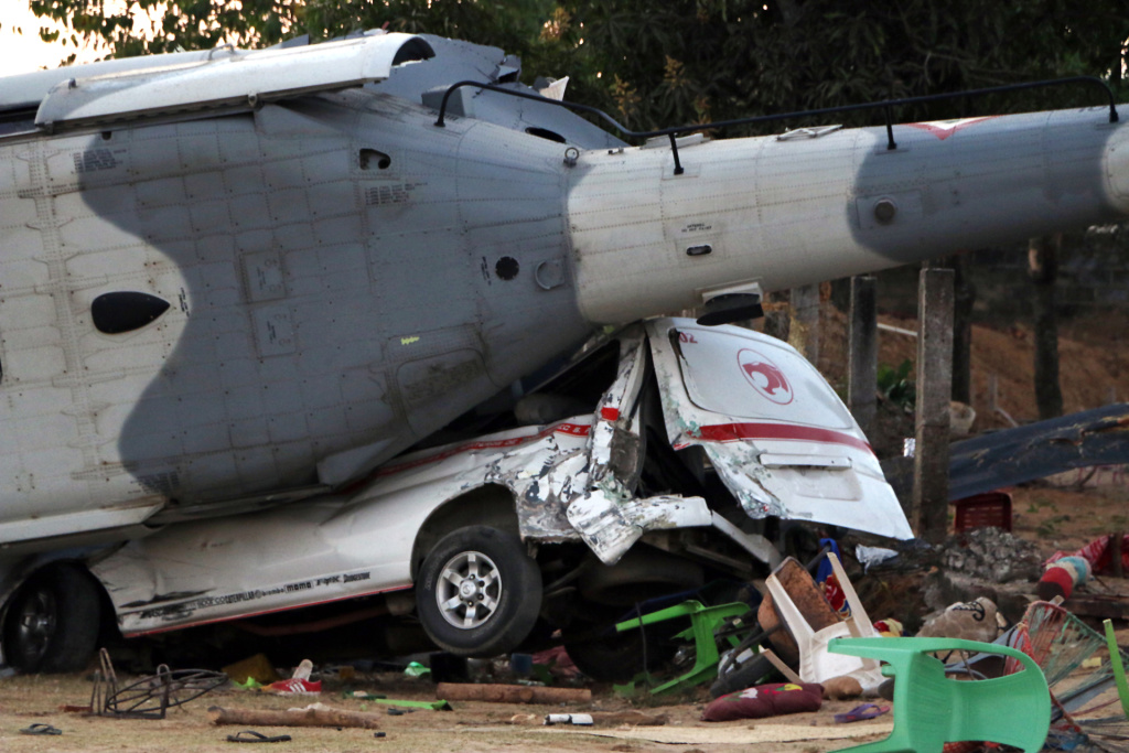 The remains of the military helicopter lay where it fell on a van in Santiago Jamiltepec, Oaxaca, Mexico, on February 17, 2018. A 7.2-magnitude earthquake rattled Mexico, causing little damage but triggering a tragedy when a minister's helicopter crash-landed on the way to the epicenter, killing 13 people, including three children, on the ground.