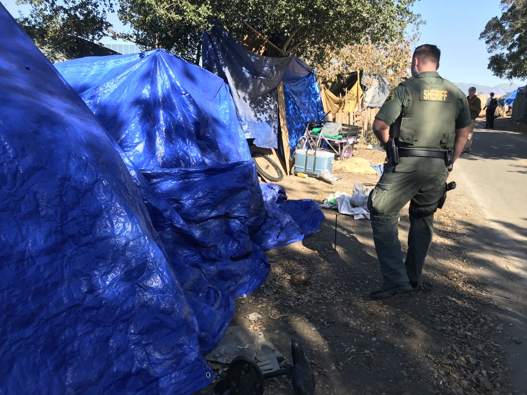 File photo: Orange County sheriff's deputies tell homeless people in early 2018 that they'll have to vacate the riverbed. On Mar. 19, 2018, the Board of Supervisors voted to open temporary shelters to house those evicted from the encampment who have been staying in motels for the past month.