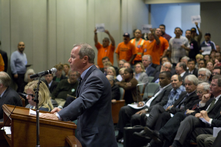 Opponents of the station at Constellation Boulevard, which would require tunneling under Beverly Hills High School, wear orange pins.