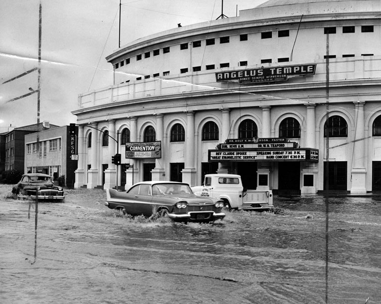 1958: The Angelus Temple, located on Glendale Boulevard near Sunset Boulevard, as flood waters lap at its doorway and cars