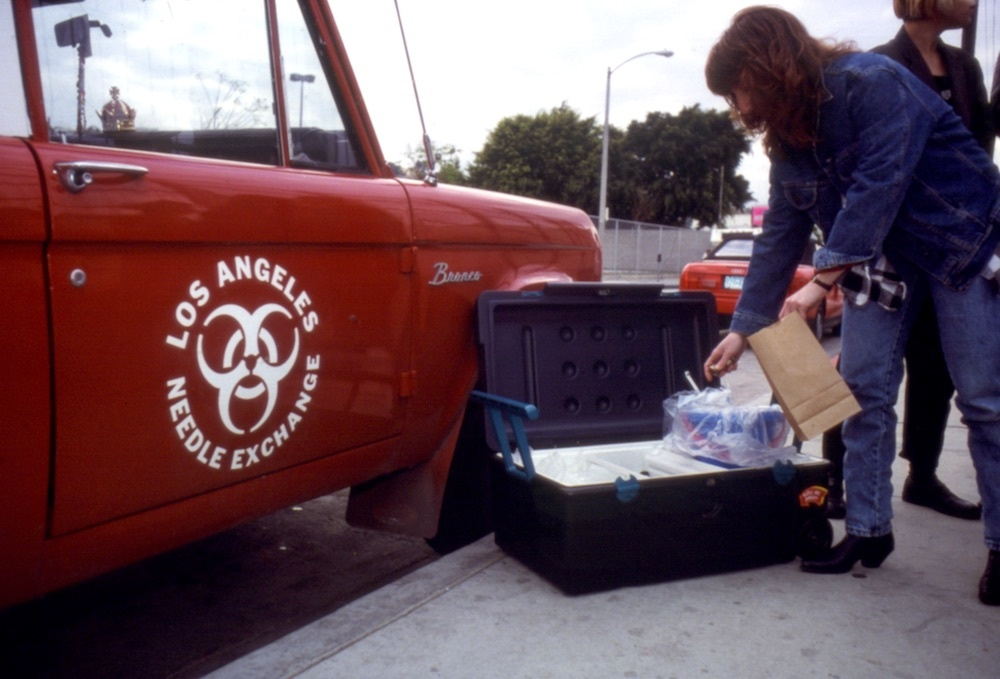 A photo shows the car ad logo used by Clean Needles Now, an L.A.-based volunteer organization that ran a needle exchange program (ca.1990)