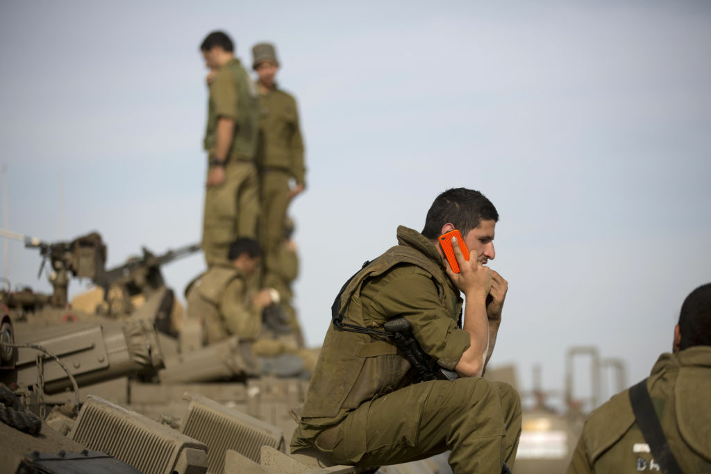 An Israeli soldier talks on his mobile phone as he sits on top of an armoured personnel carrier (APC) stationed on Israel's border with the Gaza Strip on November 16, 2012. Israeli officials said the Jewish state was preparing to launch its first ground offensive in four years into the Gaza Strip and the army started calling up reservists.
