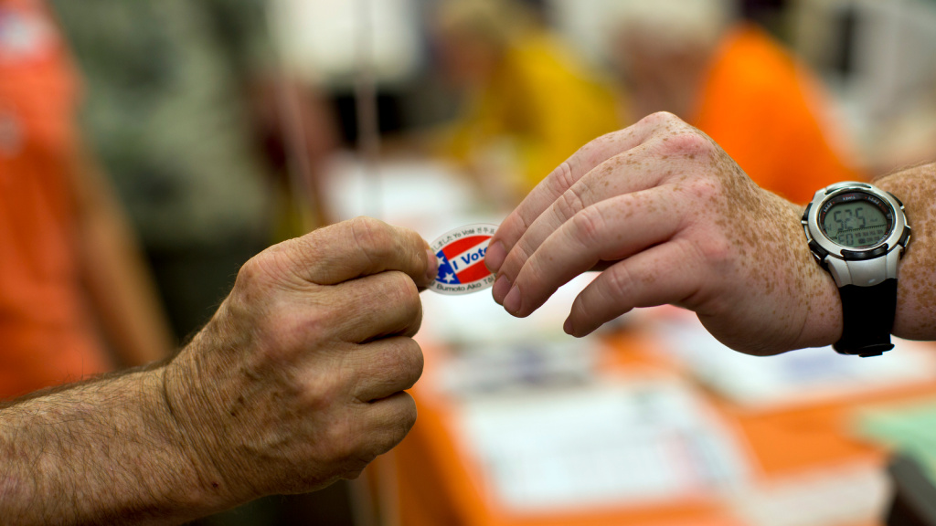 FILE: Poll clerk Patrick Meacham, right, hands a sticker to a voter at Canyon Springs School's library on Tuesday evening, June 3 in Santa Clarita.
