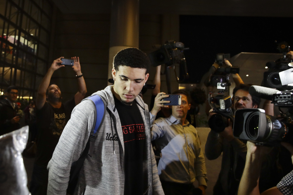 UCLA basketball player LiAngelo Ball is surrounded by the media as he leaves Los Angeles International Airport on Tuesday, Nov. 14, 2017, in Los Angeles. Three UCLA basketball players–Ball, Jalen Hill and Cody Riley–detained in China on suspicion of shoplifting returned home, where they may be disciplined by the school as a result of the international scandal.