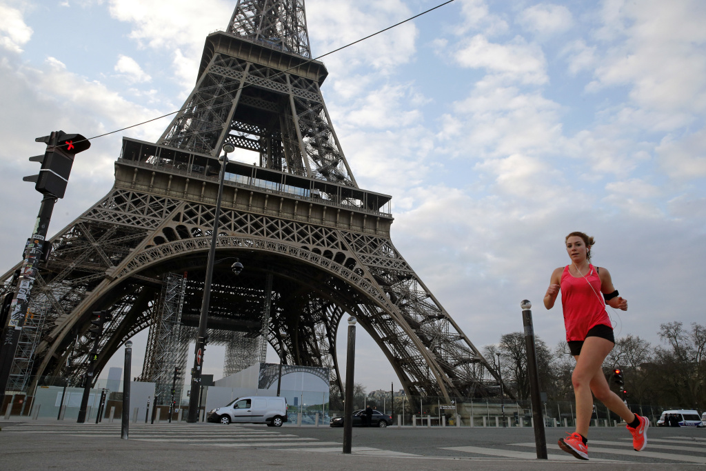 A jogger runs past the Eiffel Tower on Wednesday in Paris.