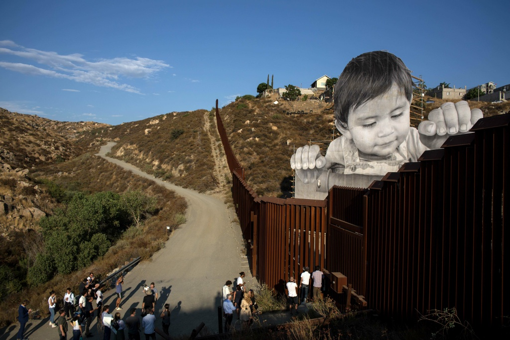 People attend the inauguration of an artwork by French artist JR on the US-Mexico border in Tecate, California, United States on September 6, 2017.