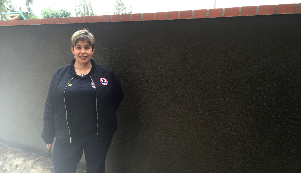 Laura Herzog stands in front of a newly stuccoed wall that will soon become a memorial to all the Americans killed in action since 9/11.